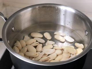 白豆沙,白芸豆放入锅中,倒入适量清水中火煮,水沸以后继续加热5分钟左右关火,将豆子倒入沥水篮中冲洗表面浮沫,再倒回锅中重新加水到没过豆子煮第二次,重复三次。