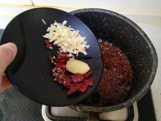 干煸豆角,倒入干辣椒、姜片、花椒、蒜末炒香。