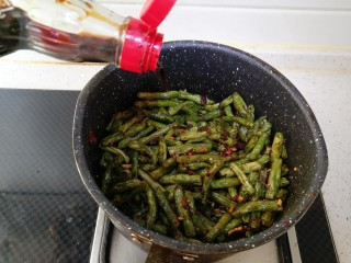 干煸豆角,倒入炸好的豆角快速翻炒半分钟左右 倒入适量酱油、盐搅拌均匀。