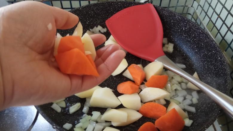 咖喱双蔬鸡,放入切好的胡萝卜和土豆块。  翻炒一会儿后,加水,没过土豆块儿块开始炖。