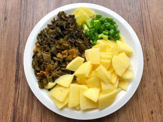 酸菜土豆烧春笋,土豆洗净切成薄片,酸菜洗净切碎,生姜去皮清洗干净切成片,葱洗净切葱段。