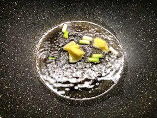 酸菜土豆烧春笋,热锅放入适量油,放入葱白和姜片炒出香味。
