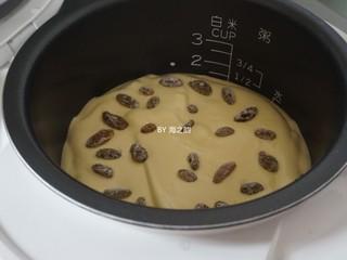 电饭锅戚风蛋糕,蛋糕糊倒入电饭锅内胆,在桌面上震两下,震出气泡,然后在上面铺上剩余的葡萄干装饰