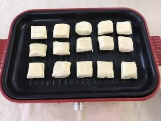 照烧豆腐,烤盘加热后,刷上一层油,然后把小豆腐码入烤盘里。