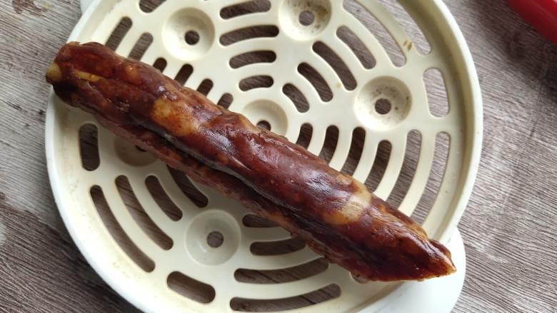 西葫芦炒腊肠,取一根腊肠,大约100克左右,洗干净之后要上锅蒸熟。