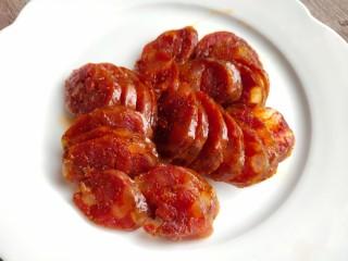 西葫芦炒腊肠,蒸熟后切成薄片装盘备用