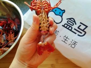 青花椒辣卤小龙虾,断生的小龙虾捞出晾一下,捏着小龙虾的尾巴最后一节,左右拧一下抽出虾线,如图。