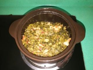 客家美食《砂锅煲咸菜酿豆腐》,放入切好的咸菜翻炒一下