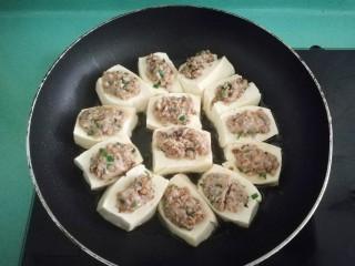 客家美食《砂锅煲咸菜酿豆腐》,煎到肉馅定型不散即可,过年时酿的多了,就全部蒸熟,然后放冰箱冷藏,想吃几个煎几个吃