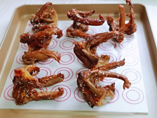 香烤鸭锁骨,烧好的鸭锁骨放入垫油纸的烤盘中。