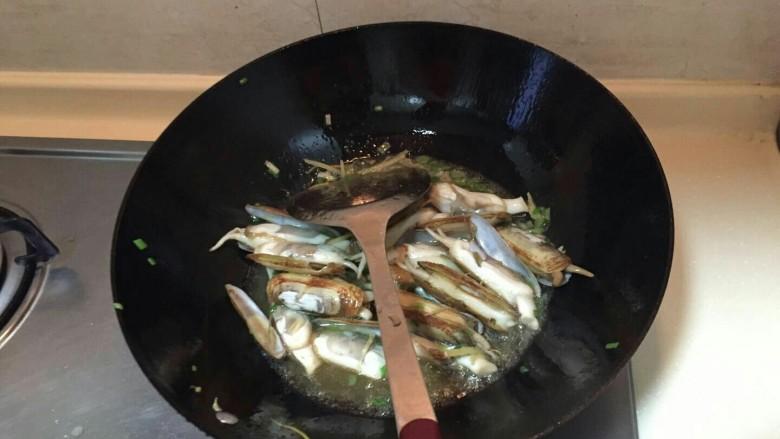 海鲜蛏子面,倒油,中火。放入小葱,再倒入蛏子翻炒2分钟