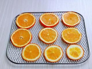 自制零添加水果干,切好的橙子片放在烤网上。