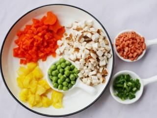 色彩缤纷的菠萝炒饭,香菇,胡萝卜,火腿,香葱切丁,豌豆剥粒。