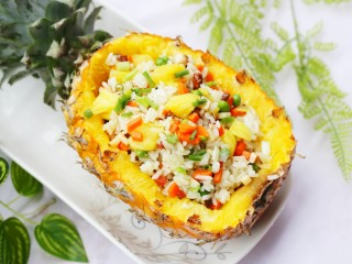 色彩缤纷的菠萝炒饭,出锅装入菠萝碗中,撒上葱花。