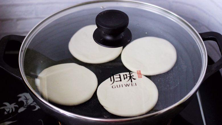 卤肉夹馍,平底锅烧热后,把擀好的面饼放入锅中。