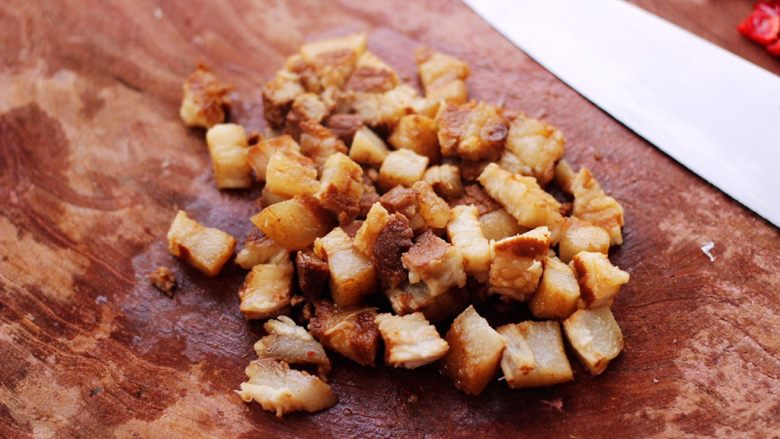 卤肉夹馍,把热好的卤花肉捞出后,用刀切成小丁。