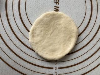 豆沙小餐包,取一面团拍扁,擀圆、翻面