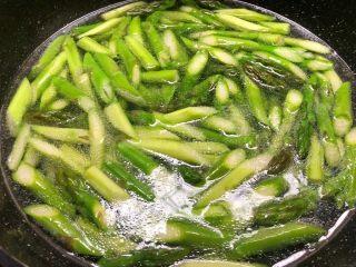 芦笋炒鱿鱼,重新放入一大碗水烧开,放入一勺油,一勺盐,少许白糖调匀,把芦笋放入焯烫30秒,捞起来用冷水冲凉待用。