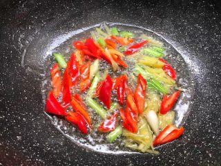 芦笋炒鱿鱼,热锅放入适量油,把葱白和姜丝放入爆香,再放入红辣椒翻炒至断生。