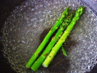 芦笋煎鸡胸肉,锅中倒入适量的清水,加入一勺盐,滴几滴橄榄油,把芦笋焯水,变色即可捞出沥干水分备用。