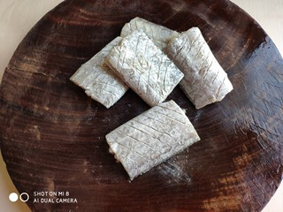 豆豉带鱼(不腥的窍门),在带鱼块表面斜着打上花刀,鱼块两面都要打上,注意不要切断鱼骨。