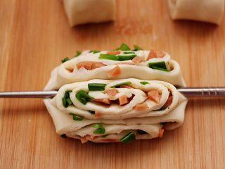 香葱火腿花卷,取一根筷子,在面卷的中间位置压一下,把花卷的两头捏紧,花卷就做好了。