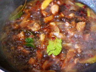 红烧牛肉炖大蒜,加入香叶,大火继续煮沸。