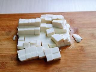 咸蛋黄虾仁豆腐,内酯豆腐倒扣在砧板上,切小块。