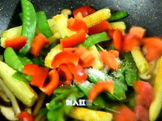 绚丽缤纷的,看着就很高级,倒入沥干的玉米笋、荷兰豆,加入盐、糖、生抽,再倒入红椒炒至断生。