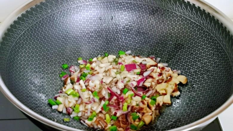 肉酱拌面,起油锅,加入洋葱煸炒,再加入香菇煸炒。