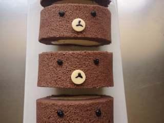 小熊熊蛋糕卷,小圆片放到嘴巴位置,可以蘸点奶油方便固定。<a style='color:red;display:inline-block;' href='/shicai/ 874/'>巧克力</a>装入裱花袋隔水融化,剪小口画出小熊的眼睛和嘴巴。
