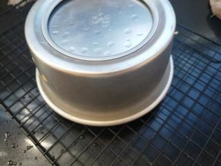 南瓜蒸蛋糕,关火,停顿一下,取出,迅速撕掉保鲜膜,倒扣在架子上。