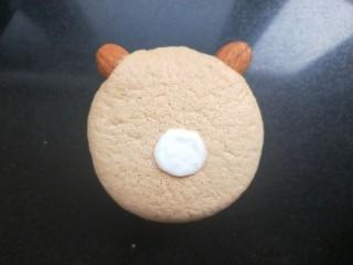 小熊纸杯蛋糕,取一个蛋糕,在顶端插入两个扁桃仁。用沙拉酱在表面偏下的位置画一个圆形。