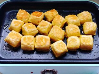 锅包豆腐,底部煎至金黄后,再翻面继续煎制。
