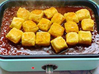 锅包豆腐,把调好的酱汁淋在豆腐上,煮开后翻炒均匀,让每一块豆腐都裹上酱汁。