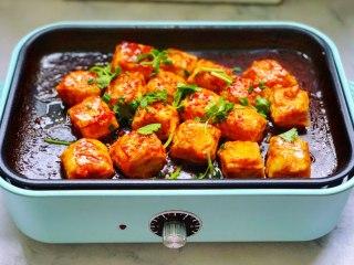 锅包豆腐,豆腐收汁后关火,撒上少许辣椒面、少许香菜和香葱。