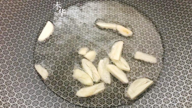 腐乳炒空心菜,大火炒锅倒油。油热后放入蒜片,炒香。