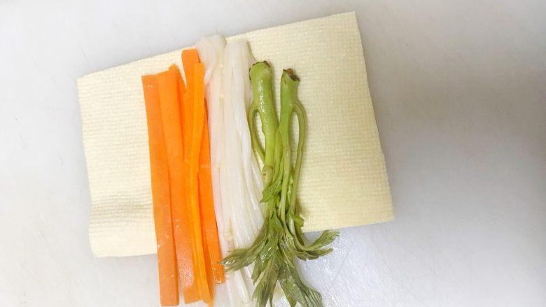 豆腐皮卷香椿,把豆腐皮放在熟食砧板上,如图在豆腐皮放上香椿,胡萝卜丝,金针菇。