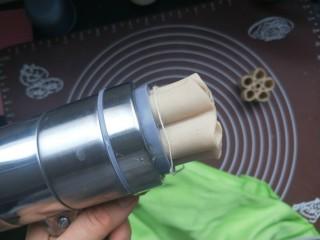 莜面窝窝(莜面栲栳栳),用力拧就会从下面挤出面来。然后大概挤三四厘米长。就停止拧,用一根棉线把莜面从根部勒断。