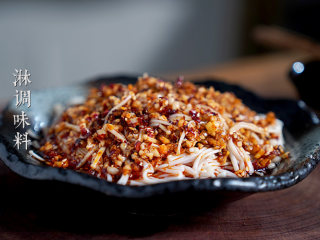 凉拌金针菇,将调味料淋在金针菇上面。