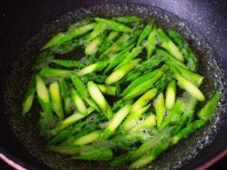 芦笋炒肉,锅里烧开水,加入少量的盐,食用油,能保持蔬菜颜色不变,把切好的芦笋,倒入烧开的水里烫至变色断生的时候,捞出备用。