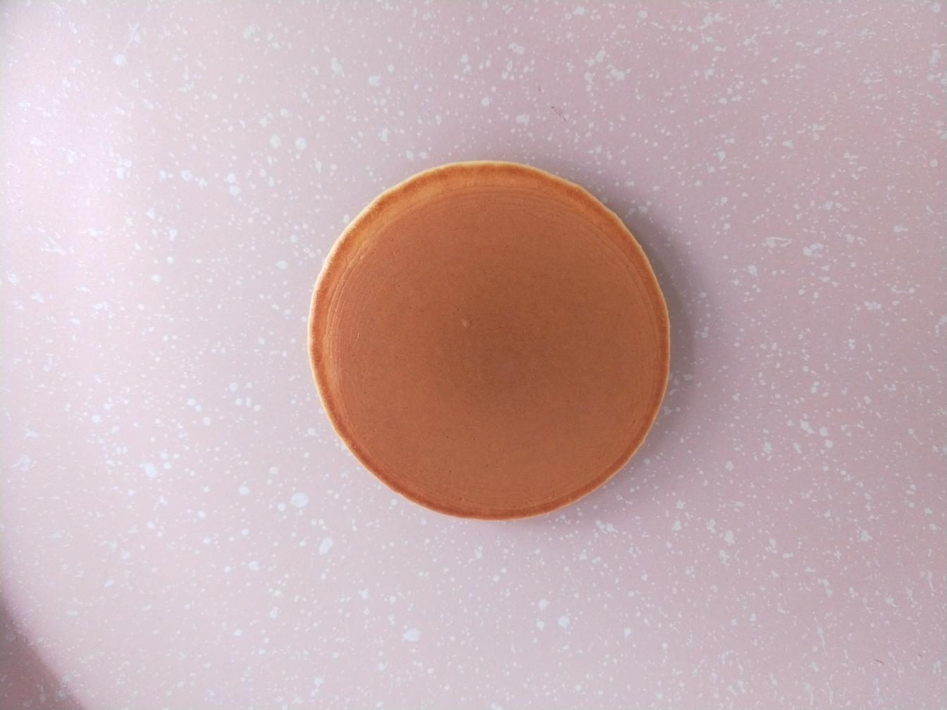 """铜锣烧(印花版),翻面,颜色刚刚好,很漂亮,翻过来煎一分钟即可。如果翻过来颜色很浅,那下一个延长一点时间,如果糊了,就缩短时间,这个自己掌控。</p> <p>然后把锅子放在湿毛巾上,听到""""滋滋""""的声音,停留两秒,给锅子降降温,然后再烙第二个。"""