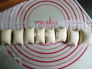 象形豆沙蘑菇包,把发酵好的面团取出,在案板上使劲揉,把面团里面的空气都揉出来,重新揉成光滑的面团。再搓成长条,切出32克小面团备用,剩余的切出8等份小面团,揉圆并盖上保鲜膜