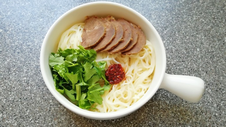 清汤牛肉面,放入碗里,摆上切好的酱牛肉和香菜,放上一勺油泼辣子(不吃辣椒可以不放)。