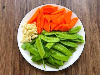 荷塘小炒,荷兰豆掐掉头尾,清新干净,胡萝卜刮掉外皮,切成薄片,蒜去皮洗净切末待用。