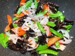 荷塘小炒,倒入焯好的荷兰豆,胡萝卜,藕片翻炒均匀,加入适量盐和适量蚝油翻炒至入味。