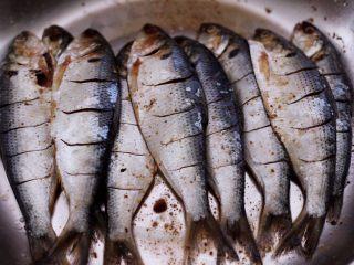 干炸海鲫鱼,用筷子搅拌均匀后,腌制半个小时。