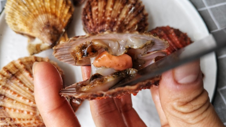 蒜蓉粉丝蒸扇贝,再用小刀将扇贝肉与壳分离。