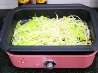 水煮牛肉,将豆芽和莴笋倒入锅中,大火炒软,铲起盛入盘中