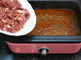 水煮牛肉,汤汁再次沸腾,将腌制上浆的牛肉均匀倒入锅里煮